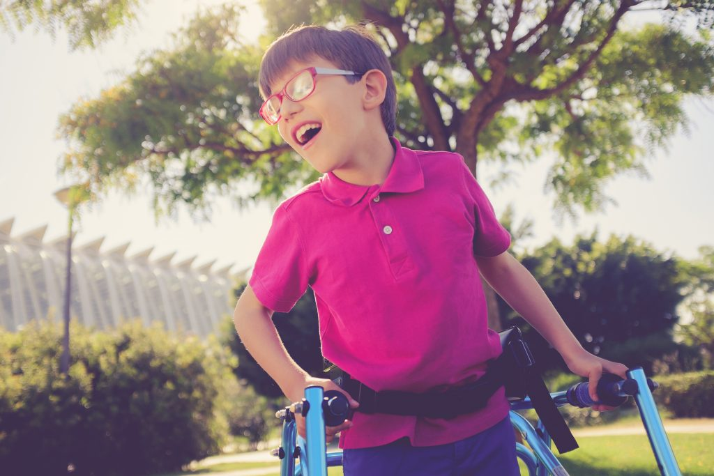 Nine year boy enjoying a walk in a sunny park using walking frame